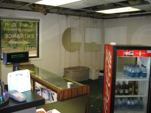 Wet display case, wet Coke box, wet rug, mold on the walls.